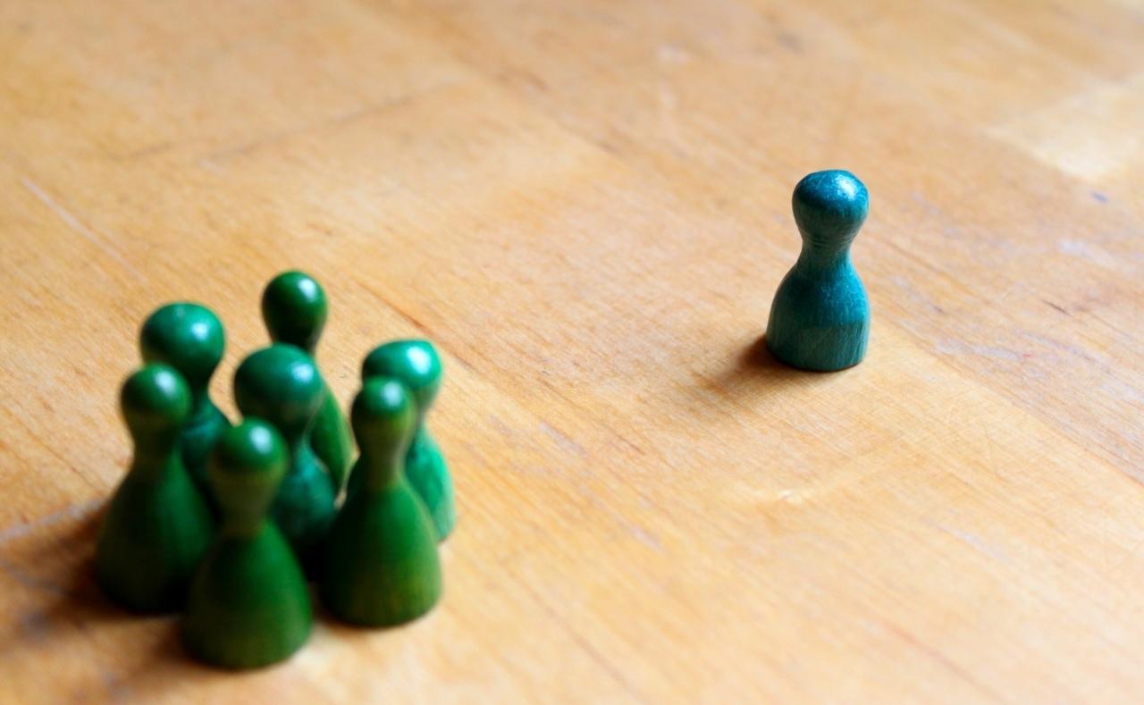 Blauwe pion op afstand van een groep groene pionnen