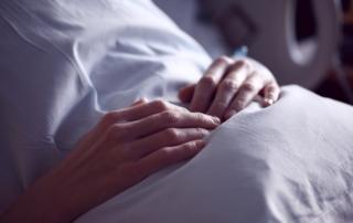 Handen boven de lakens op de buik in een ziekenhuisbed.